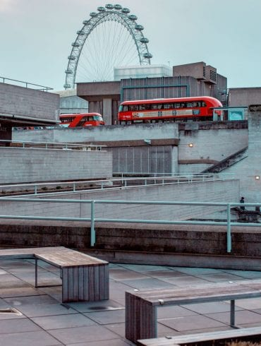 National Theatre exterior looking west with London buses crossing Waterloo Bridge